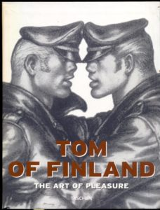 Cover of 'Tom Of Finland: The Art of Pleasure' art book by Taschen featuring two men in motorcycle leathers with faces close together as though they're about to kiss.
